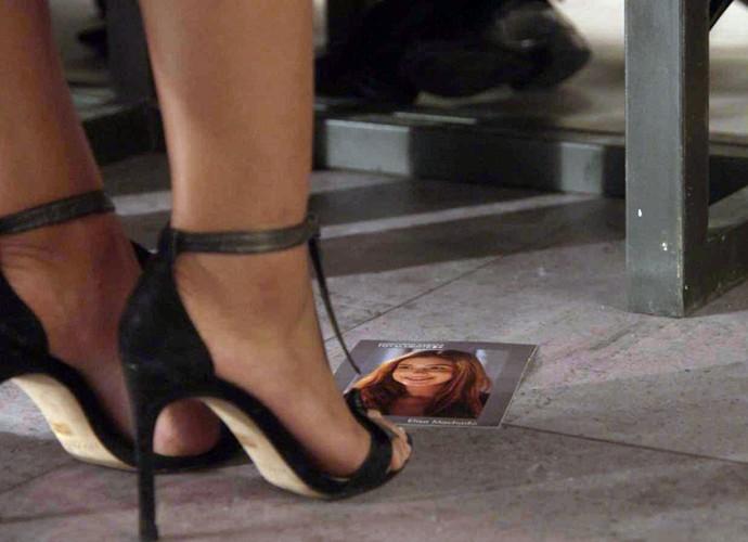 Na hora de mostrar a pilha de fotografias, a imagem de Eliza acaba caindo no chão e só Carolina percebe (Foto: TV Globo)