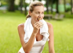Mulher comendo barra de cereal euatleta (Foto: Getty Images)