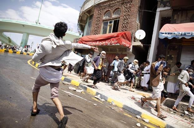 Manifestante joga pedra em policiais durante confronto próximo à Embaixada dos EUA no Iêmen, em Sanaa, nesta sexta-feira (14) (Foto: AFP)