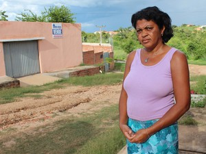 A dona de casa Maria da Conceição diz que o marido chega a jogar areia e pedras para tapar buracos (Foto: Patrícia Andrade/G1)