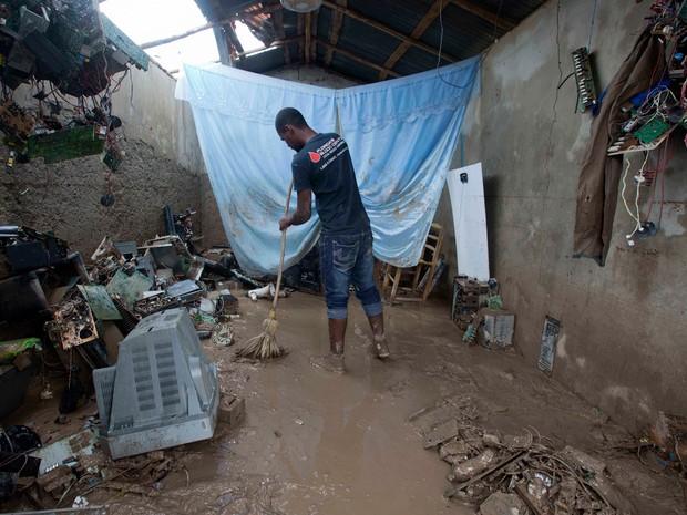 Professor limpa casa após passagem do furacão Matthew por Les Cayes, no Haiti (Foto: AP)