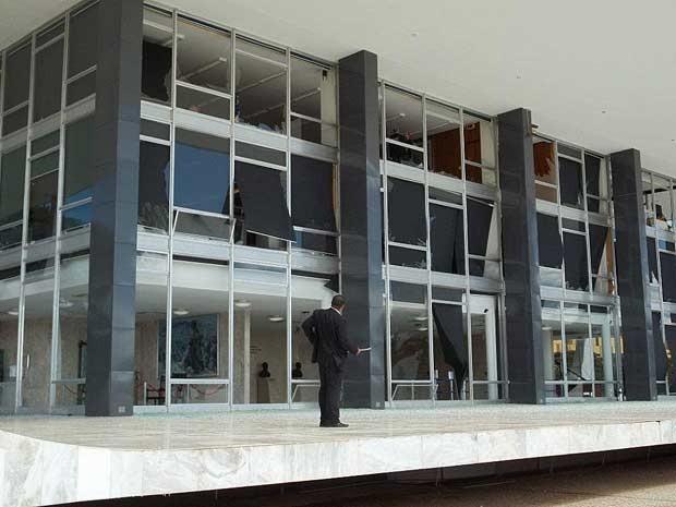 Segurança olha fachada de vidro do Supremo destruída após passagem de caça da FAB em voo rasante neste domingo (1) (Foto: Fausto Carneiro/G1)