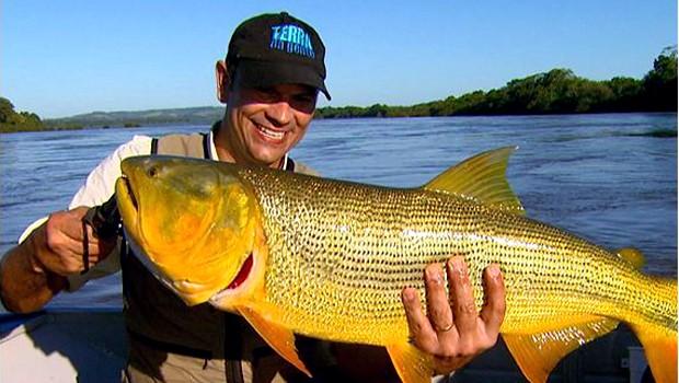 Repórter Eduardo Lacerda mostra o dourado fisgado (Foto: Reprodução EPTV)