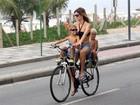 De biquíni e shortinho, Fernanda Lima pedala e leva os filhos na garupa