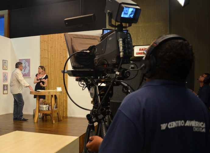 Apresentador do É Bem Mato Grosso, Pescuma conversa com a ilustradora, Camila no palco do programa (Foto: Luana Daubian)