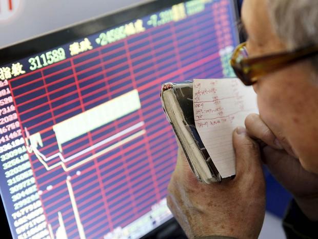 Um investidor acompanha de perto na tela de um monitor o andamento da bolsa de valores após novo acionamento do 'circuit breaker', mecanismo que paralisa o pregão, nas bolsas chinesas de Xangai e Shenzen, em Xangai, na China (Foto: Reuters/China Daily)