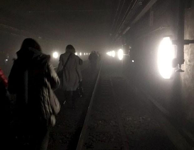 Passageiros caminham por trilhos após atentado no metrô de Bruxelas (Foto: Reuters)