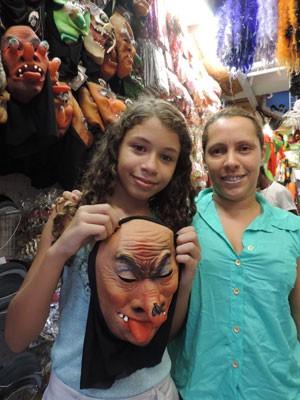 A estudante Ana Clara e a mãe dela, Carina, mostram máscara vendida em loja no Centro do Recife (Foto: Rafael Dias / G1)