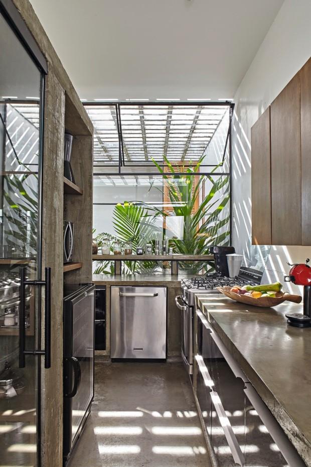 """Cozinha. O núcleo de concreto aparente abriga o espaço, que ganha luminosidade extra com os elementos vazados. """"De qualquer ambiente dá para ver um jardim"""", diz Anna Juni (Foto: Victor Affaro / Editora Globo)"""