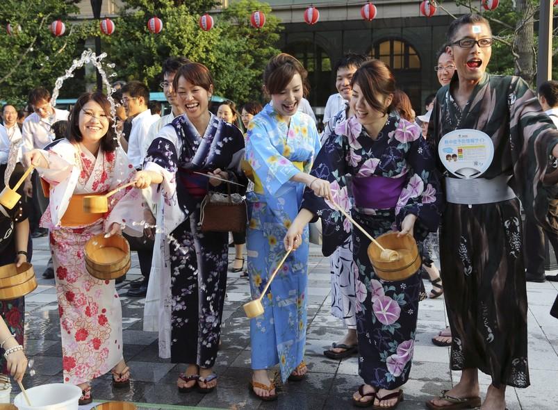 Pessoas vestindo yukata, ou quimono de verão, borrifam água em uma rua de uma área de escritórios durante um evento anual de verão em Tóquio. O ato pretende que as pessoas superem as altas temperaturas. Na cidade, os termômetros marcavam 35ºC