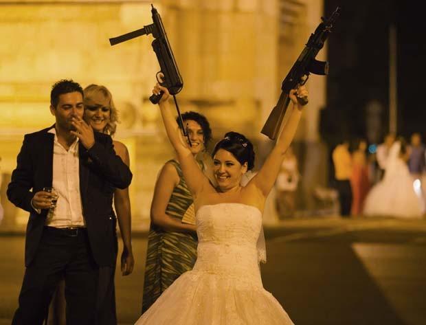 Noiva posa com armas dos 'sequestradores' (Foto: Vadim Ghirda/AP)