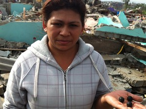 Dona de casa Maria Telma Freires, 29 anos, exibe balas de borracha e diz que irmão de 10 anos se feriu (Foto: Tatiana Santiago/G1)