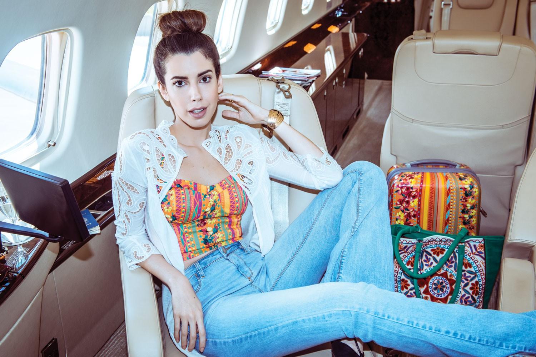 Camila Coutinho usa jaqueta de renda (R$ 200), top cropped (R$ 80), calça jeans (R$ 130) e bracelete (R$ 60) da coleção que assina para a Riachuelo. Ao fundo, mala (R$ 400) e bolsa (R$ 190) (Foto: Fred Othero e Candice Lake; styling Tiago Jucá)