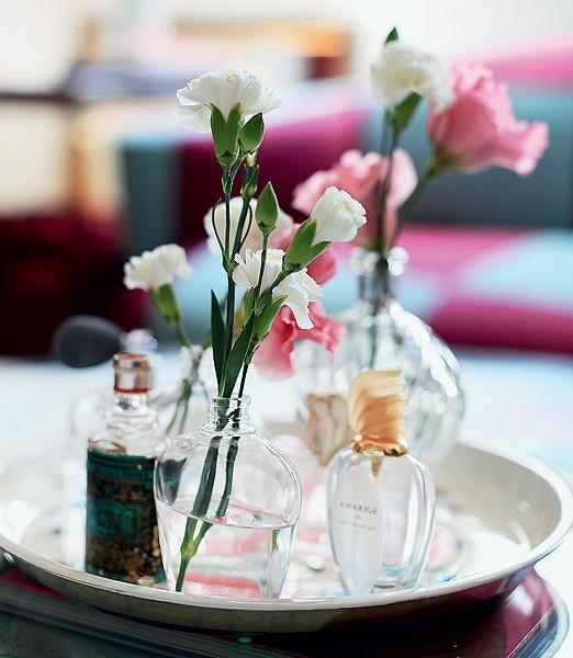 O que restou do perfume foi só a embalagem? Ótimo! Os frascos reunidos seguramente chamam mais atenção que vasos comuns com flores – na foto, cravínea branca e lisianto rosa (Foto: Rogério Voltan)