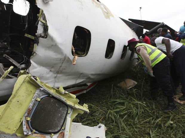 Equipe de resgate trabalha no local onde um avião nigeriano que levava passageiros caiu pouco depois da decolagem em Lagos, por uma falha no motor, provocando pelo menos oito mortes. (Foto: Sunday Alamba/AP)