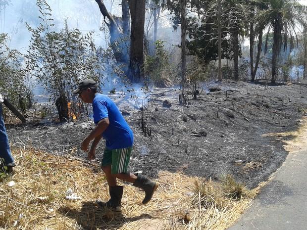 Moradores tentando apagar fogo com baldes de água (Foto: Jussara Santa Rosa/TV Clube)