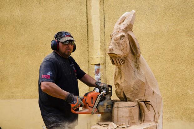 Homem usa motosserra para fazer escultura em madeira durante festival na Alemanha (Foto: Thomas Peter/Reuters)
