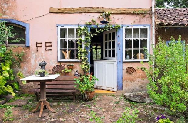 Nos fundos da casa, o tom rosado das paredes desgastadas e o azul das portas e das janelas remetem a uma imagem bucólica, quase europeia. A palavra fé foi feita com estacas de ferro originais dos trilhos de trem da maria-fumaça que passava em frente  (Foto: Lufe Gomes / Editora Globo)
