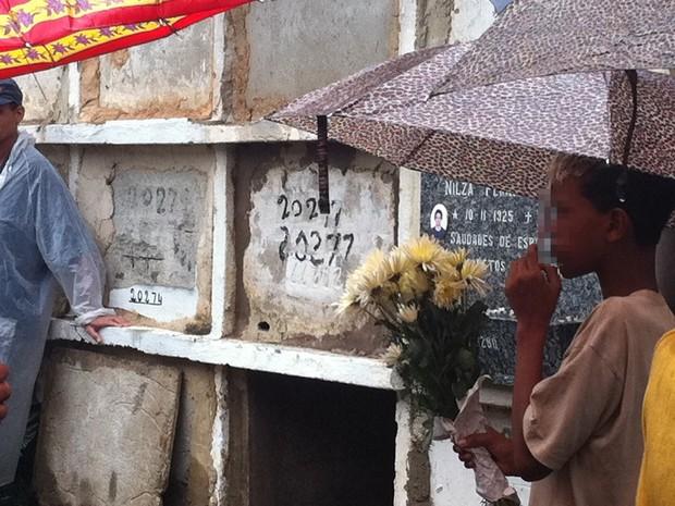 Irmão de Rafael, atropelado na Avenida Brasil, carrega flores no enterro  (Foto: Tássia Thum/G1)