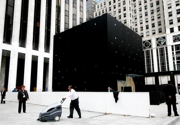 Inauguração da Apple Store da Quinta Avenida, em  Nova York, em maio de 2006:  oculto sob a lona estava o cintilante cubo de vidro de dez metros de altura que guarnece a entrada subterrânea da loja. O projeto arquitetônico remete à pirâmide do Louvre, do  (Foto: Mark Lennihan)