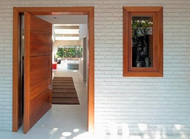 A entrada do lar ganhou porta pivotante e janela em madeira de cumarú da Martin Esquadrias. Passadeira Fields da By Kamy (Foto: André Fortes/Divulgação)