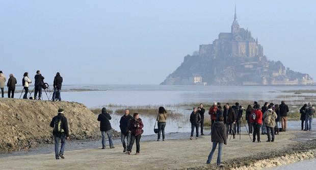 Monte Saint-Michel é visto ao fundo em foto deste sábado: maré alta deve encobrir ligação de monte com continente  (Foto: AP Photo)