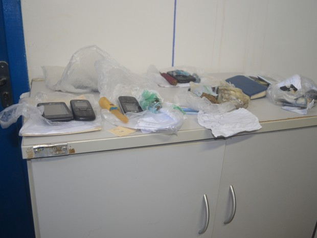 Drogas, facas e celulares apreendidos (Foto: Rogério Aderbal/G1)