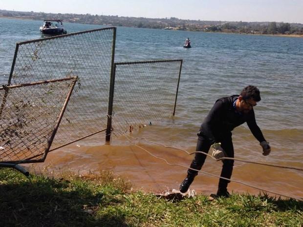 Homem trabalha na retirada de grades instadas dentro do lago Paranoá (Foto: Gabriel Luiz/G1)
