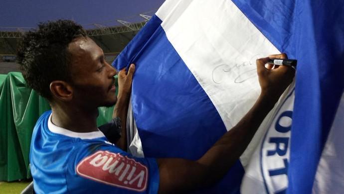 Atacante Marquinhos autografa bandeira de torcedor após treino do Cruzeiro, em Puerto Ordaz (Foto: Marco Astoni)