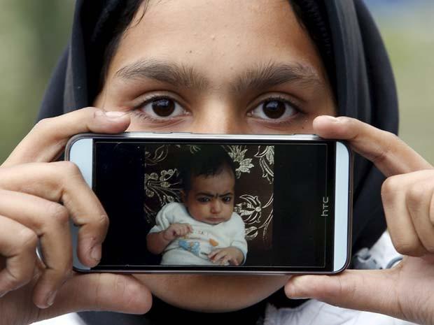 Rubina, de Cabul, no Afeganistão, mostra foto da sobrinha enquanto espera na fronteira da Eslovênia com a Áustria (Foto: REUTERS/Srdjan Zivulovic)
