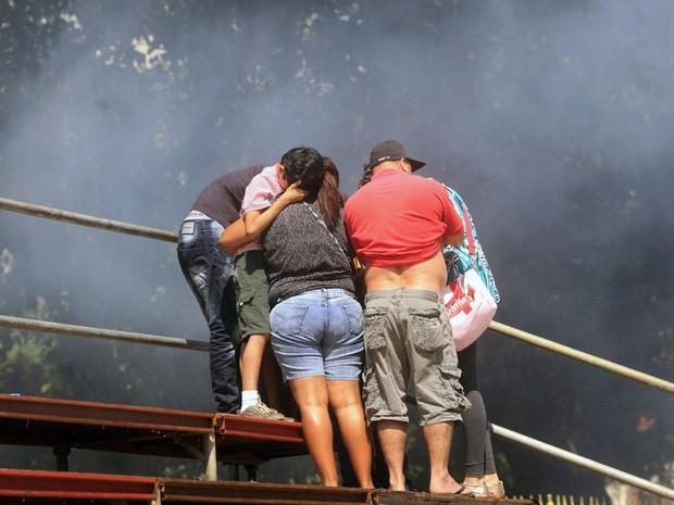 Família 'ilhada' em arquibancada tenta se proteger do gás lacrimogêneo tacado pela polícia durante confronto em meio ao desfile do 7 de Setembro no Rio de Janeiro. (Foto: Ricardo Moraes/Reuters)