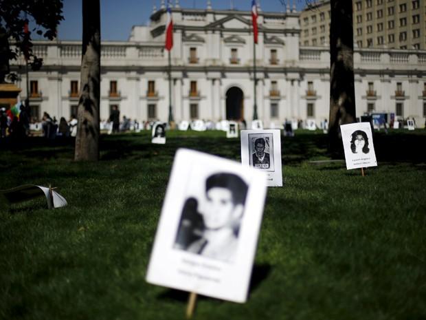 Fotos de vítimas da ditadura de Augusto Pinochet são espalhadas em frente ao palácio presidencial, em Santiago, na sexta (11), data do 42º aniversário do golpe que depôs o presidente Salvador Allende (Foto: Reuters/Ivan Alvarado)