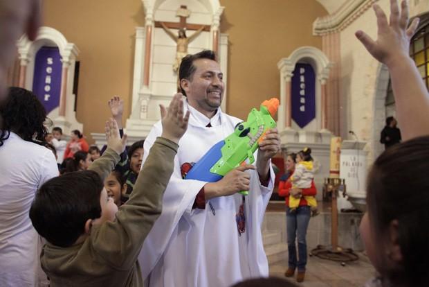Padre Humberto segura a arma de brinquedo com água benta durante a missa (Foto: Daniel Becerril/Reuters)