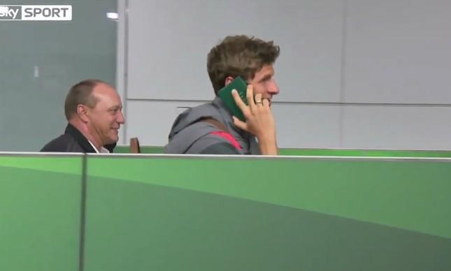 Thomas Müller saca o passaporte e o improvisa como telefone para evitar a imprensa