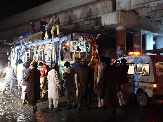 Voluntários inspecionam ônibus em que bomba explodiu nesta segunda-feira (19) em Quetta, no Paquistão (Foto: AFP PHOTO / BANARAS KHAN)