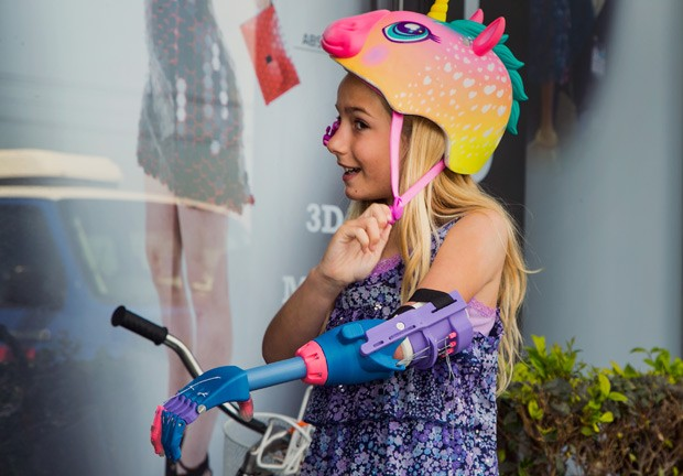 Faith Lennox ajusta seu capacete: prótese a ajudou a andar de bicicleta  (Foto: AP Photo/Damian Dovarganes)