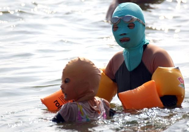 Mulher e criança aproveitam praia de Qingdao. (Foto: AFP)