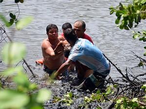 Bombeiros retirou a criança do mangue (Foto: Walter Paparazzo/G1)