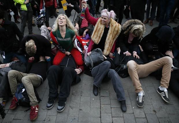 Grupo participa de sentada na cara coletiva em frente ao Parlamento britânico (Foto: Stefan Wermuth/Reuters)
