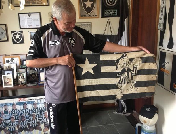 Seu Hércules mostra a primeira bandeira do Botafogo, que ganhou do pai, em 1968, quando o time foi bicampeão carioca (Foto: Ana Cláudia Gonçalves/GLOBOESPORTE.COM)