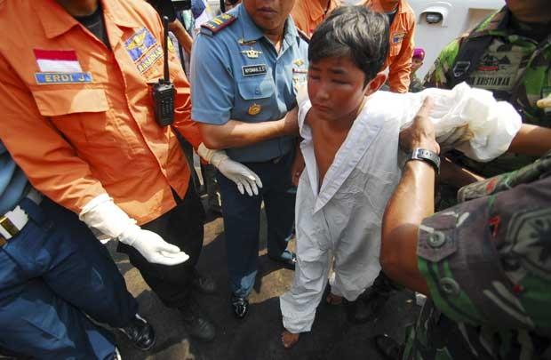 Equipe de resgate da província Banten, na Indonésia, ajuda garoto que sobreviveu à queda de uma embarcação com imigrantes ilegais que ia para a Austrália (Foto: AP)