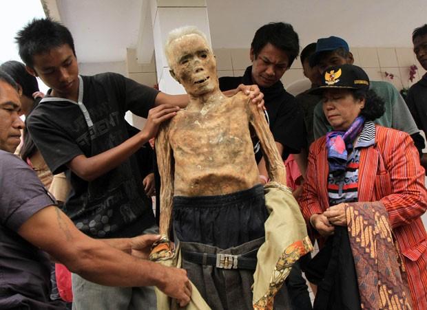 Familiares dão roupas novas ao corpo preservado de um parente morto durante um ritual chamado Ma'nene em Tana Toraja, na ilha indonésia de Sulawesi. (Foto: Elang Herdian/AP)