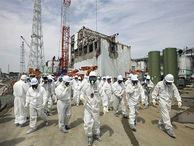 Jornalistas e funcionários da Tokyo Electric Power Co. (Tepco) usam roupas especiais durante visita, em maio, à usina Nuclear de Fukushima. (Foto: Tomohiro Ohsumi / Pool / Reuters)