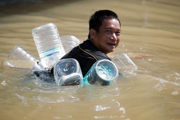 Tailandês usou como uma espécie de colete salva-vidas garrafões de plástico vazios (Foto: Nicolas Asfouri/AFP)