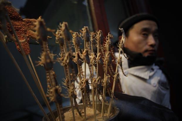 Vendedor comercializa espetinhos de escorpião em Pequim, na China. (Foto: Eugene Hoshiko/AP)