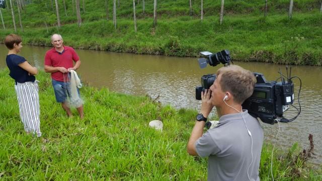 Janine Limas e Rogério Danielsk durante gravação com pescador  (Foto: Saimon Novack/Divulgação)