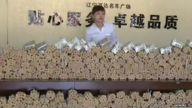 Comprador optou por forma de pagamento 'atípica' após ter acumulado grande quantidade de trocados em posto de gasolina onde trabalha (Foto: Liaoning TV/ BBC)