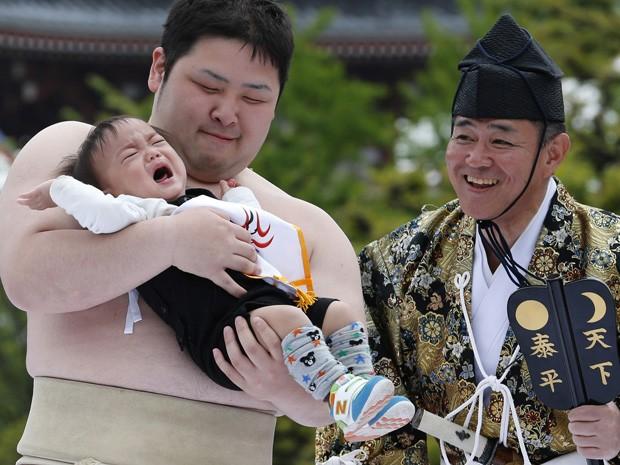 Lutador de sumô segura criança durante concurso de choro de bebê (Foto: Shizuo Kambayashi/AP)