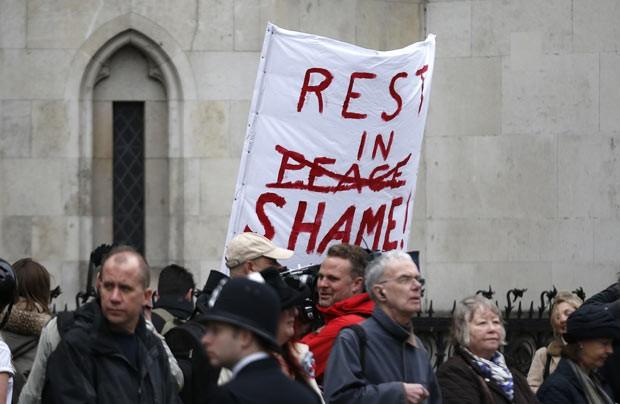 Manifestante com cartaz contra Margareth Thatcher em rua de Londres nesta quarta-feira (17); 'Descanse em vergonha', diz o texto (Foto: AFP)