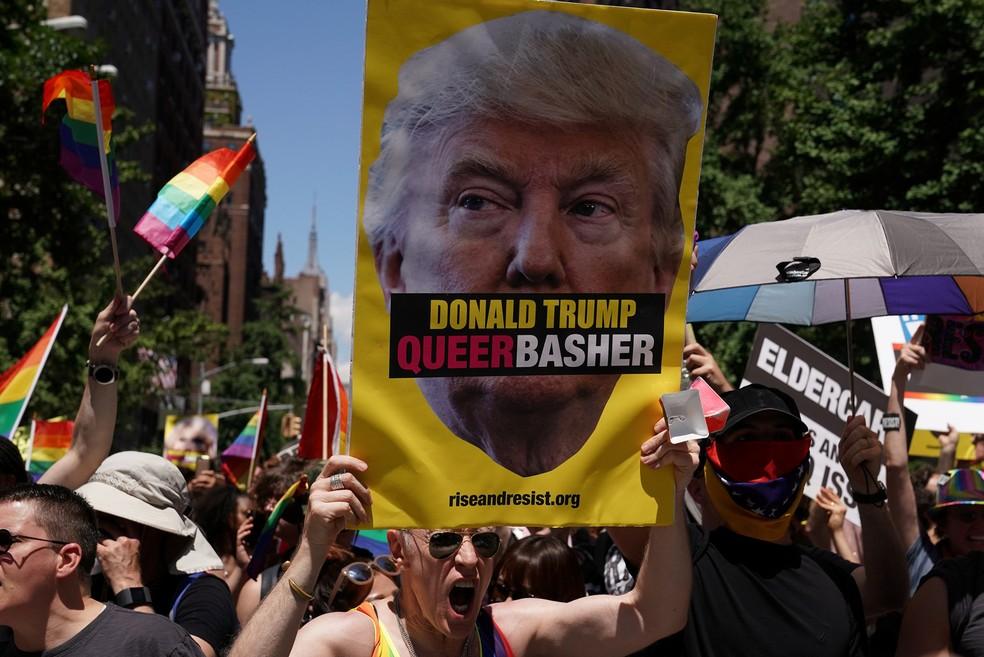 Homem exibe cartaz contra o presidente dos EUA Donald Trump durante a parada LGBT em Nova York (Foto: Carlo Allegri/Reuters)